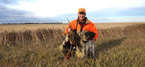 Hunter with dog and pheasant